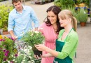 Florist at garden centre selling potted flowers to young couple