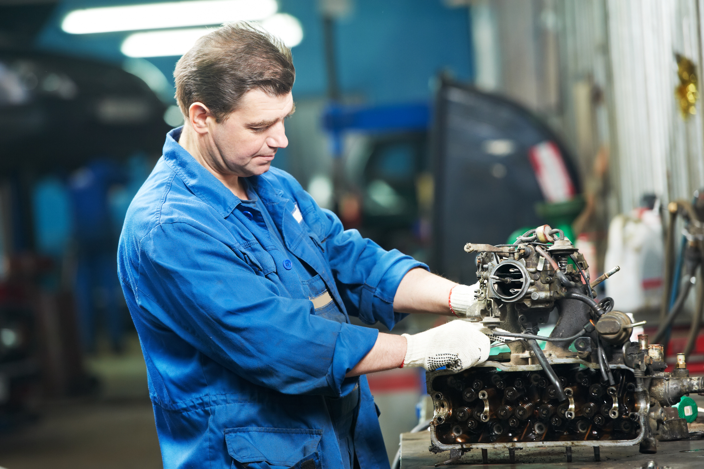 automotive mechanic disassembling car engine with spanner during automobile maintenance at repair service station